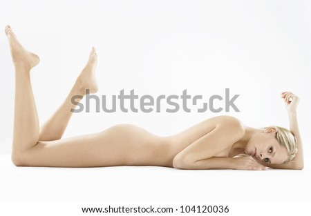 Woman's full naked body laying down on a white background. - stock photo