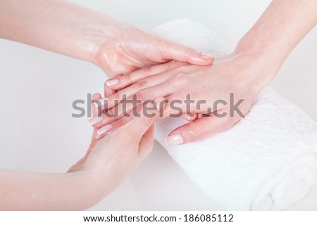 Woman's hand and nails oil massage at beauty salon - stock photo