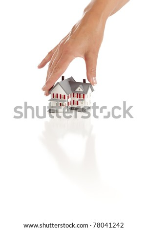 Woman's Hand Choosing A Home on a White Background. - stock photo