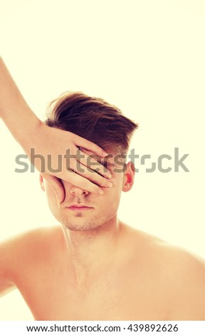 Woman's hand covering man's eyes. - stock photo