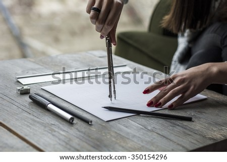 Woman's hand drawing with caliper  - stock photo