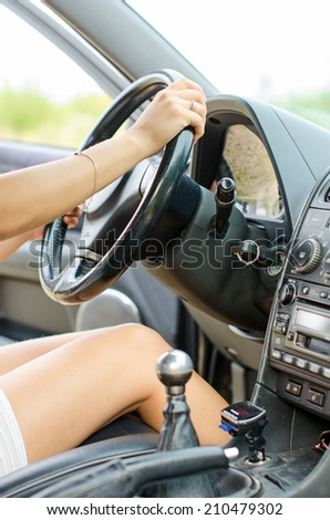Woman's hand driving a car. Unrecognizable person. - stock photo
