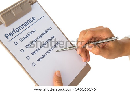 Woman's hand fills out performance checklist on white