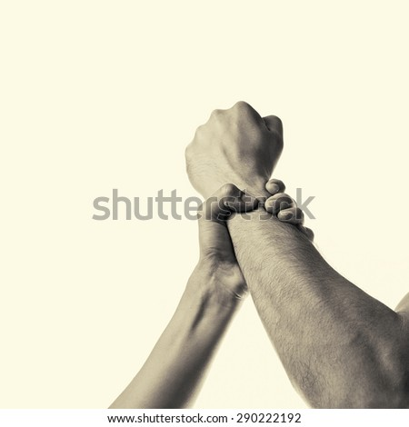 woman's hand gripping a man's fist stopping aggression - stock photo