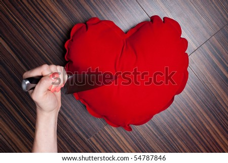 Woman's hand holding a knife to a heart pillow - stock photo