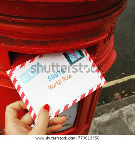 Womans hand holding letter santa north stock photo royalty free womans hand holding a letter to santa north pole near the red post box spiritdancerdesigns Images