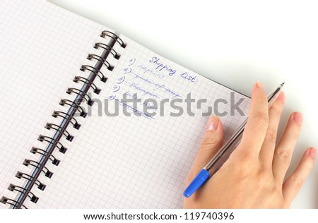 woman's hand holding a notebook with a shopping list close-up - stock photo