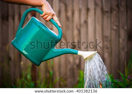 Womanâ??s hand holding a watering can pouring water
