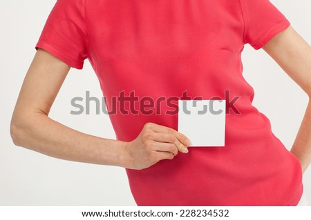 Woman's hand holding blank white sticker over bright red t-shirt - stock photo