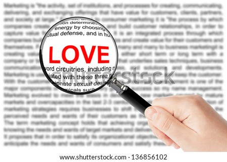 Woman's hand, holding classic styled magnifying glass, with Love sign - stock photo