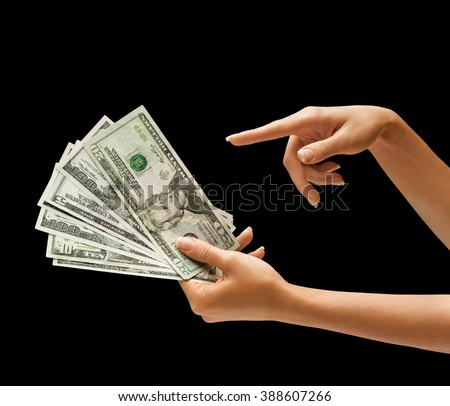 Woman's hand holding dollars money and points finger at the money isolated on black background - stock photo