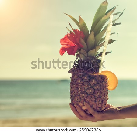 Woman's hand holding exotic pineapple cocktail. - stock photo