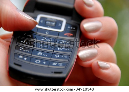 Woman's hand holding mobile phone keypad
