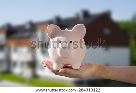 Woman's hand holding piggybank. New house in background - stock photo