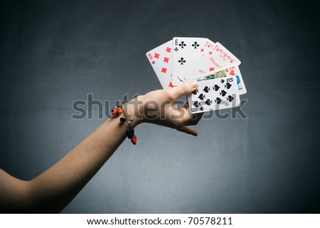 woman's hand holding playing cards on dark background - stock photo