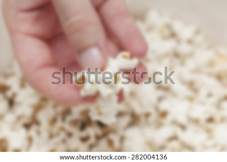 Woman's hand holding pop corns in a bowl. Post processed with blur filter.  - stock photo