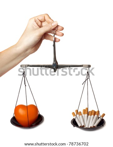 """Woman's hand holds the scales with orange heart and cigarettes isolated on white background. """"Concept - harm of smoking"""". - stock photo"""