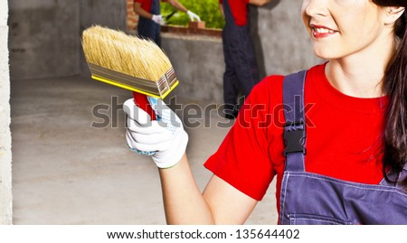 woman's hand in glove with brush paints a reinforced concrete wall - the background is out of focus - two men with bricks and masonry trowel