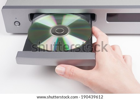 Woman's hand Inserting a disc into a CD player - stock photo