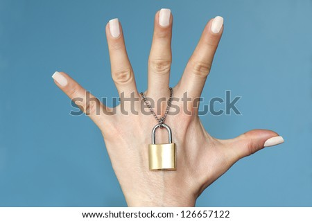 Woman's hand linked with chain and padlock - stock photo