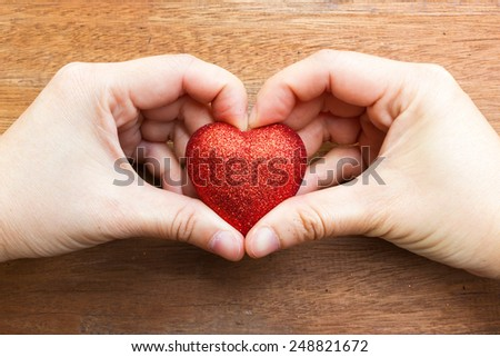 Woman's hand make a heart shape and holding a red heart shape. On wooden background. Top view.