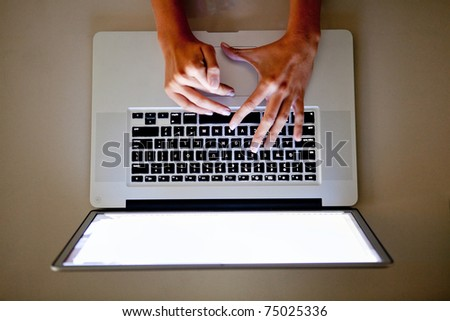 Woman's hand on the keyboard of a laptop computer