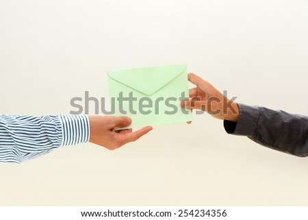 woman's hand passes a green envelope to male hand on white background view 2 - stock photo