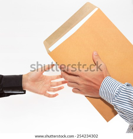 woman's hand passes a yellow envelope to male hand on white background view 1 - stock photo