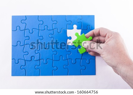 Woman's hand placing green Jigsaw puzzle piece in blue puzzles signifying diversity and equality decision making and problem solving - stock photo