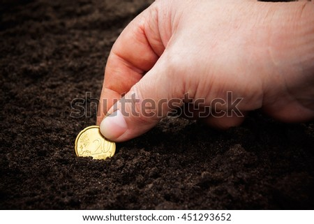 Woman's hand planting coin in soil. Selective focus