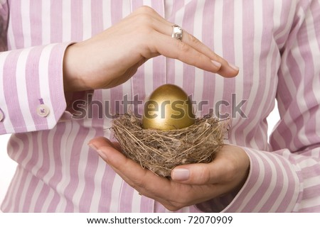 Woman?s hand protecting a nest with a golden egg inside