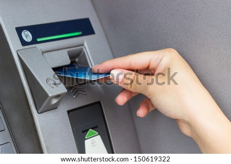Woman's hand puts credit card into ATM, close up