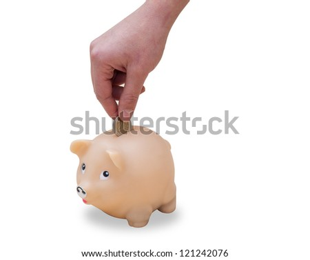 woman's hand putting coins in a piggy bank