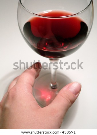 Woman's hand reaching for Wine Glass - stock photo