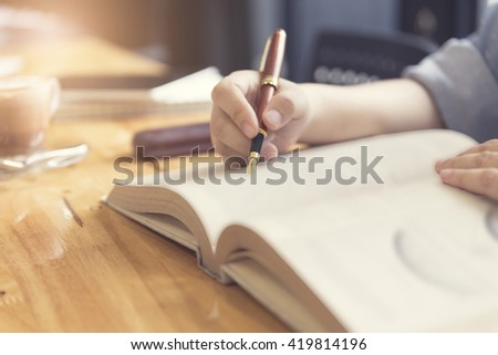 woman's hand reading book with pen, tablet and notebook on wooden table, selective focus and vintage tone