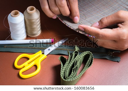 Woman's hand sewing quilt with sewing equipments - stock photo