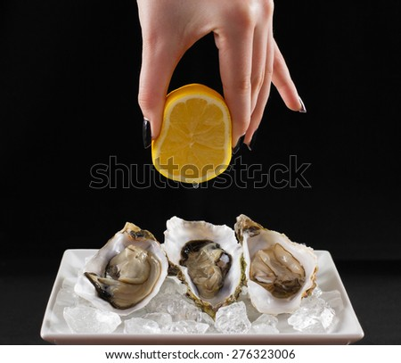 Woman's hand squirt three oyster shell with lemon juice, dark background - stock photo