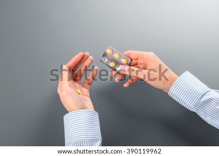 Woman's hand taking pill. Woman has abnormal heart rate. This one cures allergy. Remember the dosage. - stock photo