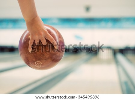 Woman's hand throwing ball in bowling club. - stock photo