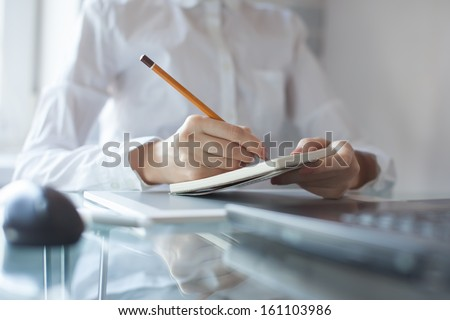 Woman's hand using a pencil noting on notepad - stock photo
