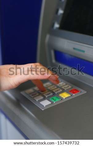 Woman's hand using ATM machine, focus on little finger - stock photo