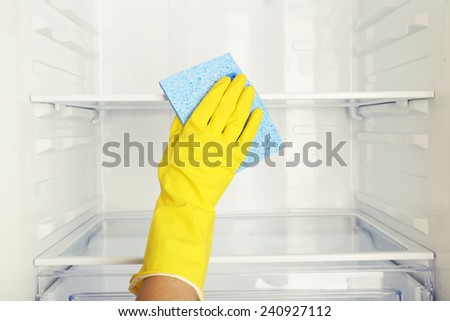 Woman's hand washing refrigerator with duster - stock photo