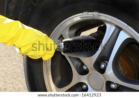 Woman's hand with a rim brush cleaning a wheel of an SUV car