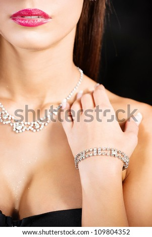 woman's hand with bracelet on breasts on dark background - stock photo