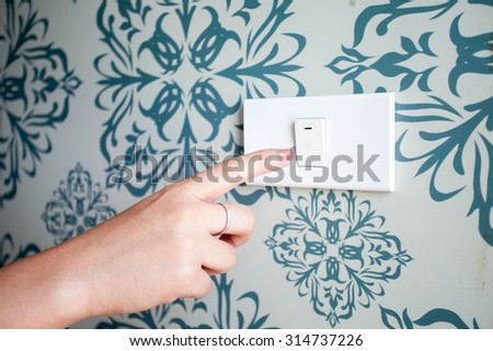 Woman's hand with finger on light switch to turn off the lights. - stock photo