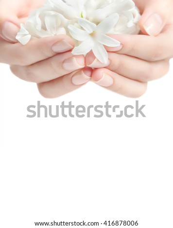 Woman's hand with nude nail manicure and white hyacinth flowers. Close up, selective focus. Copy space. - stock photo