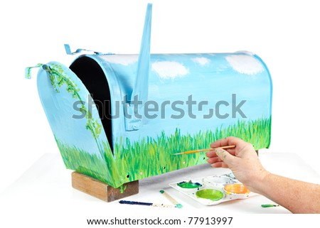 Woman's hand with paint tray & brush working on hand painting a mailbox