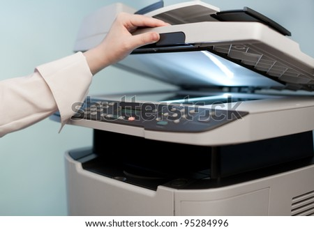 Woman's hand with working copier (focus on finger)