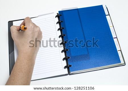 Woman's hand writing on agenda/Managing calendar - stock photo