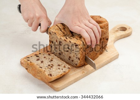 woman's hands are slicing fresh bread by a knife on a wooden table board